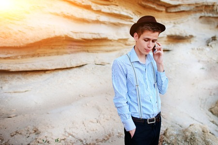 sand quarry: Attractive man is standing in the middle of a sand quarry and making a call from a smartphone.