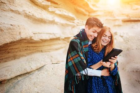 mapa de procesos: Hermosa mujer y hombre guapo envuelto en una manta. Sonriendo y mirando la pantalla de una tableta en el fondo de una cantera de arena.