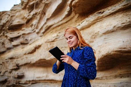 sand quarry: Beautiful woman smiling and looking at the screen of a tablet on the background of a sand quarry. Stock Photo