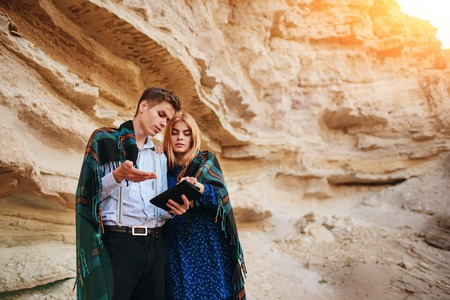 sand quarry: Beautiful woman and handsome man wrapped in a blanket. They are smiling and looking at the screen of a tablet on the background of a sand quarry.