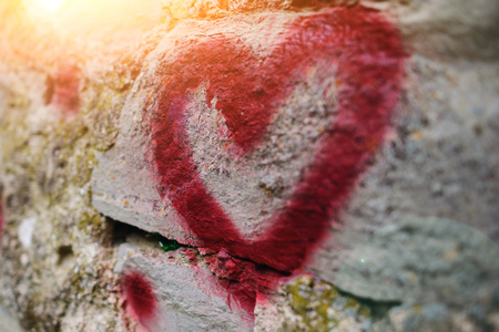 textured wall: Close up background graffiti silhouette of red heart on an old relief stone wall. Stock Photo