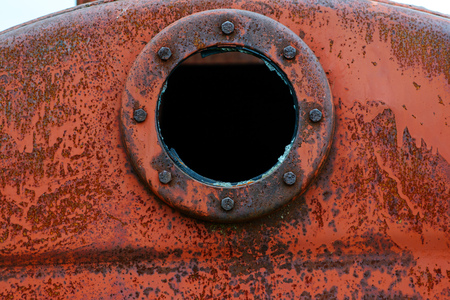 Close up background of rusty metal tank with rusty circular hole.