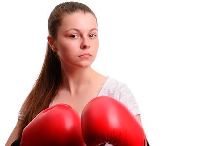 A young sports woman-boxer poses to the camera in red boxing gloves. She concentrates and standing in the battle rack.