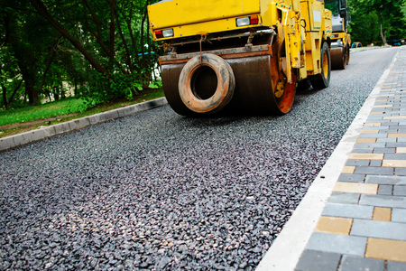Het uitvoeren van reparatiewerkzaamheden: het stapelen van asfaltrollen en het warmdrukken van asfalt. Machinebouwweg.