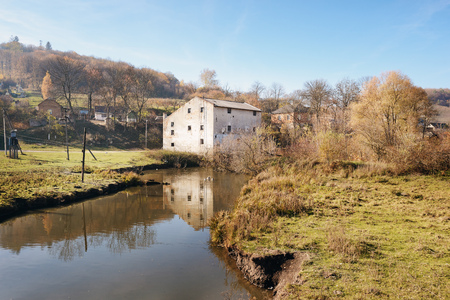 Autumn landscape of the countryside: old non-working watermill near greenfields and flowing river. Stock Photo