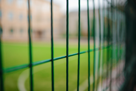 Close up metallic net-shaped green fence on a background of football field.