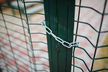 Close up metallic net-shaped green fence that closed and wrapped by chain. Stock Photo