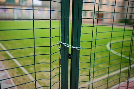 Close up metallic net-shaped green fence that closed and wrapped by chain on a background of school football field. Stock Photo