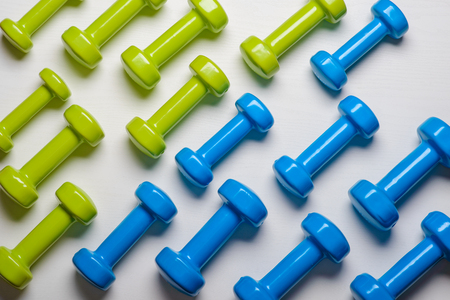 many blue and green dumbbells on a white background ,concept preparing to fitness sports equipment top view mock up.