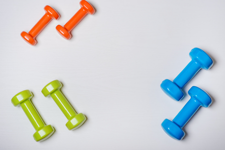 many blue green and one orange in the middle dumbbells on a white background ,concept preparing to fitness sports equipment top view mock up.