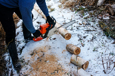 Process of sawing log by chainsaw in the winter . Stockfoto