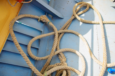 a piece of blue rope lies on a beach. Stock Photo