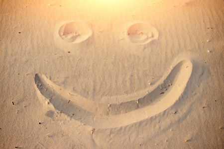 A smiley face drawing on a sand. Stock Photo