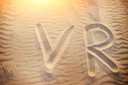 The word VR is written on the sand on a wonderful sunny day.