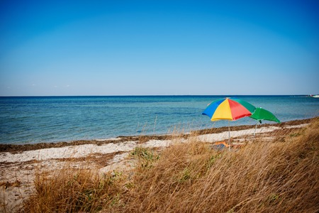 umbrella on the beach with cloudy blue sky in background.