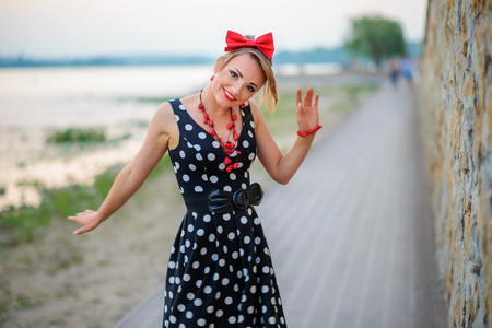 A girl in a dress is dancing happily in the outside.