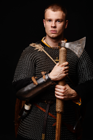 Male medieval warrior in armour and chain mail, viking with battle ax in hands . Stockfoto