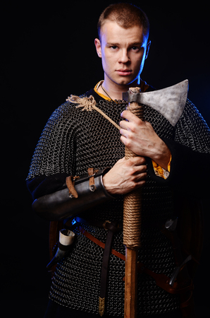 Male medieval warrior in armour and chain mail, viking with battle ax in hands . Stock Photo - 102487063