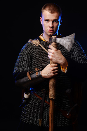 Male medieval warrior in armour and chain mail, viking with battle ax in hands . Stock Photo - 102487065