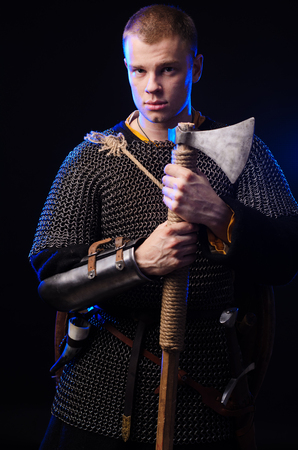 Male medieval warrior in armour and chain mail, viking with battle ax in hands . Stock Photo