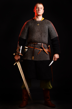 A soldier in a chain of letters stands with a sword in his hands on a black background. Stock Photo - 102487068