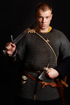 A soldier in a chain of letters stands with a sword in his hands on a black background. Stock Photo - 102487067