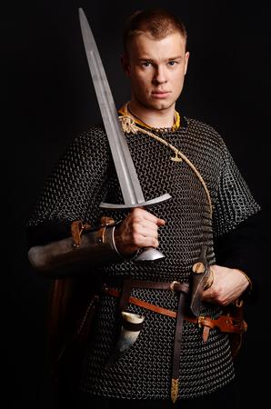Un soldado en una cadena de letras se encuentra con una espada en sus manos sobre un fondo negro.