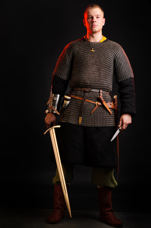 A soldier in a chain of letters stands with a sword in his hands on a black background. Stock Photo - 102487076