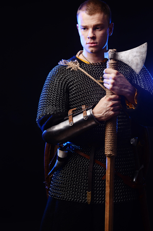 Male medieval warrior in armour and chain mail, viking with battle ax in hands . Stock Photo - 102487074