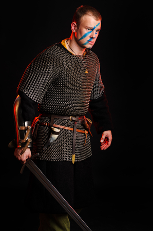 A soldier in a chain of letters stands with a sword in his hands on a black background. Stock Photo - 102487080