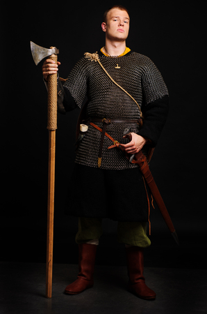 Male medieval warrior in armour and chain mail, viking with battle ax in hands . Stock Photo - 102487513