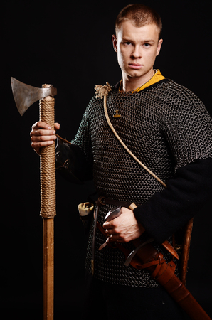 Male medieval warrior in armour and chain mail, viking with battle ax in hands . Stock Photo - 102487512