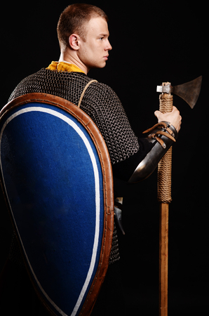 Warrior Stand his back to the camera with a shield on his back and an ax in his hands. Stockfoto