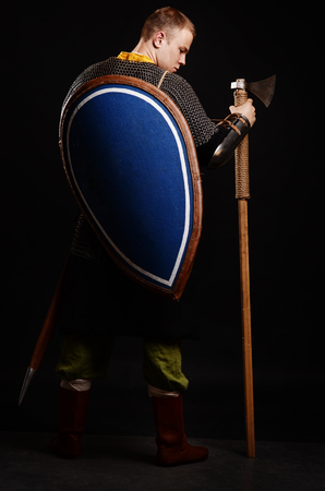 Warrior Stand his back to the camera with a shield on his back and an ax in his hands. Stock Photo