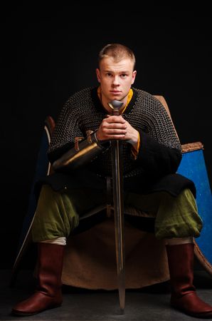 A soldier in a chain of letters is sitting holding a sword in his hands. Stock Photo - 102487442
