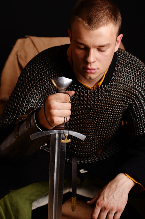 A soldier in a chain of letters is sitting holding a sword in his hands.