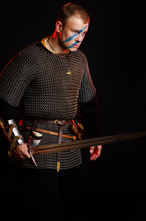 A soldier in a chain of letters stands with a sword in his hands on a black background. Stock Photo - 102487403
