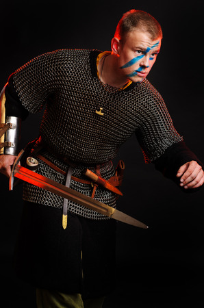 A soldier in a chain of letters stands with a sword in his hands on a black background. Stock Photo - 102487408