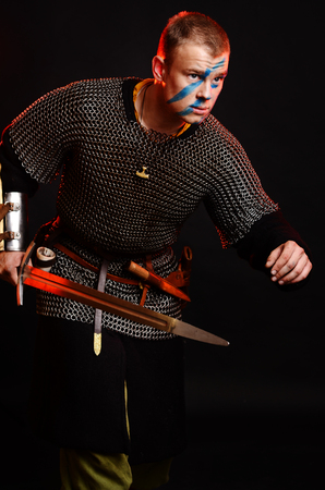 A soldier in a chain of letters stands with a sword in his hands on a black background. Stockfoto