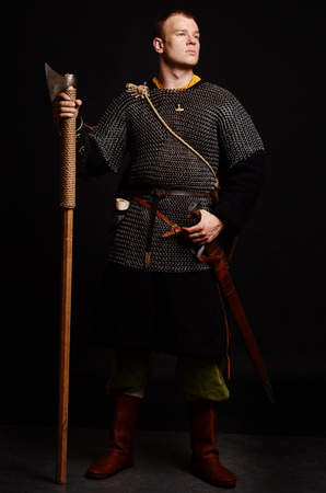 Male medieval warrior in armour and chain mail, viking with battle ax in hands . Stock Photo - 102487659