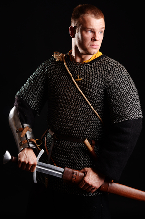 A soldier in a chain of letters stands with a sword in his hands on a black background. Stock Photo