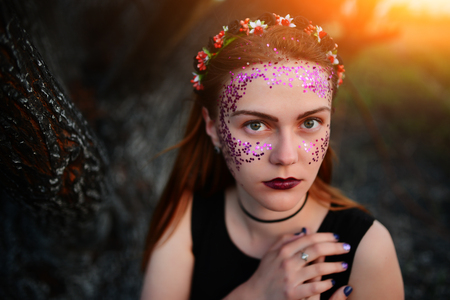 A young beautiful woman with a violet shine on her face stands near a burnt tree.