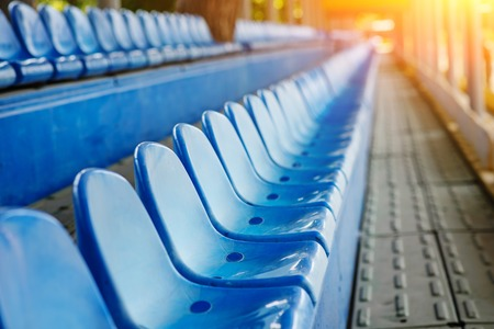 Empty plastic chairs in the stands of the stadium.