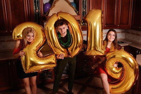 New 2019 Year is coming. Group of cheerful young people carrying gold colored numbers and have fun at the party. Archivio Fotografico