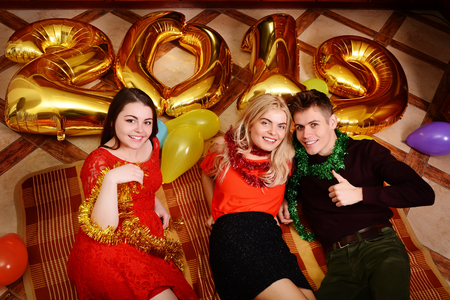 New 2019 Year is coming. Group of cheerful young people carrying gold colored numbers and have fun at the party. Stock Photo