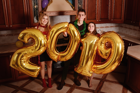 New 2019 Year is coming. Group of cheerful young people carrying gold colored numbers and have fun at the party. Stock fotó