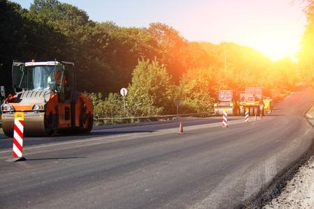 Carrying out repair works: asphalt roller stacking and pressing hot lay of asphalt. Machine repairing road. Archivio Fotografico - 118032596