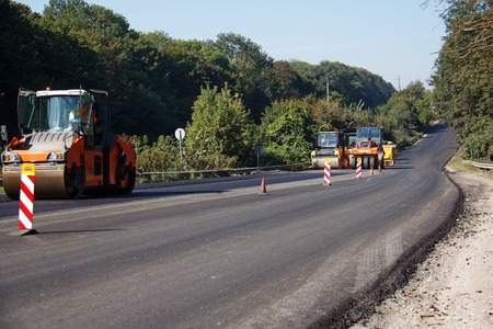 Carrying out repair works: asphalt roller stacking and pressing hot lay of asphalt. Machine repairing road. Stock Photo