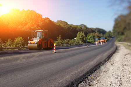 Carrying out repair works: asphalt roller stacking and pressing hot lay of asphalt. Machine repairing road. Archivio Fotografico