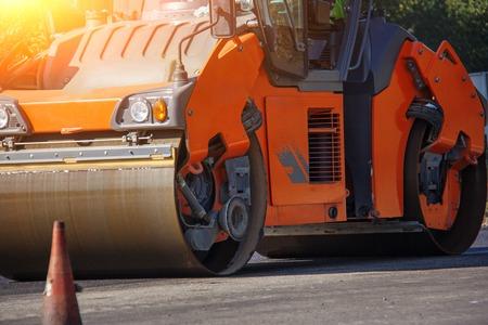 Carrying out repair works: asphalt roller stacking and pressing hot lay of asphalt. Machine repairing road. Archivio Fotografico - 118032607